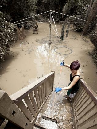Alice Richter-Ward cleans mud from her Brisbane back yard during the January 2011 floods.