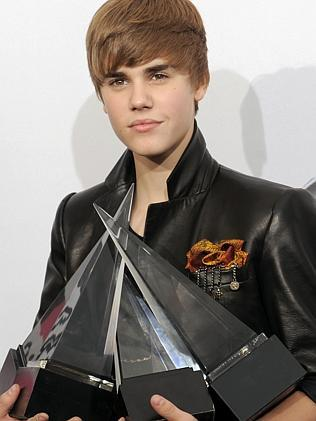 The boy next door ... Bieber poses with his awards backstage at the 38th Annual American Music Awards in 2010 in Los Angeles. (AP Photo/Chris Pizzello)