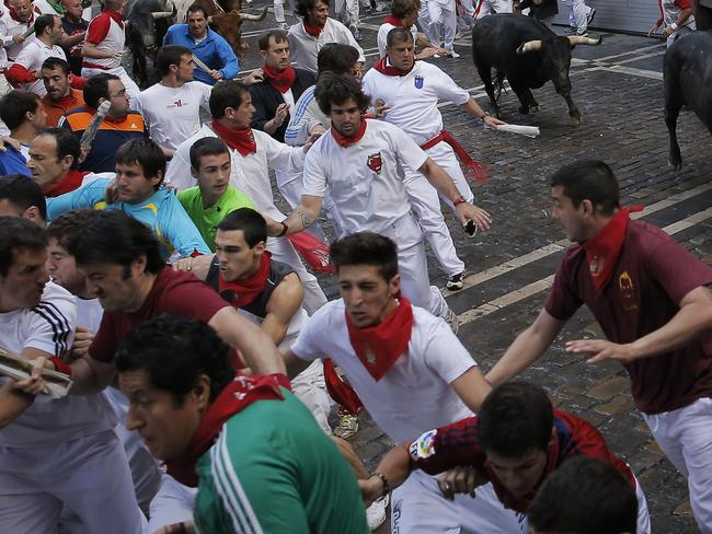 Miura fighting bulls run after revelers during the running of the bulls at the San Fermin festival, in Pamplona, Spain, Monday, July 14, 2014. Revelers from around the world arrive in Pamplona every year to take part in some of the eight days of the running of the bulls. (AP Photo/Andres Kudacki)