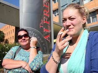 Joanne and Brogan light up cigarettes outside The Alfred Hospital.Picture:Ian Currie