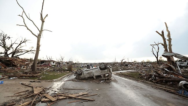 A vehicle lies upside down in the road after a powerful tornado ripped through the area on May 20, 2013 in Moore, Oklahoma.