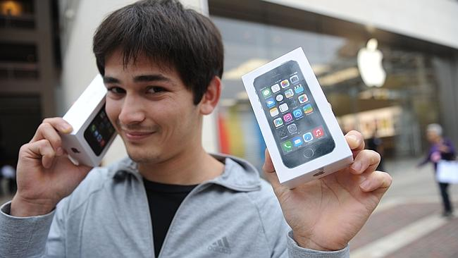 Kerim Muhammet poses with his two new Apple iPhone 5S after waiting in line overnight to be among the first to make the purchase, outside the Apple Store at the Americana at Brand shopping complex in Glendale, California. Picture: AFP