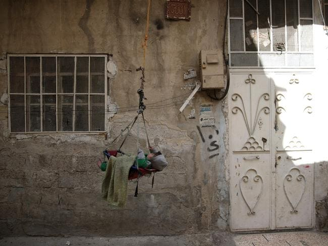 A baby is suspended on a swinging- rope outside a house in the rebel-held suburb of Tishreen on the outskirts of the Syrian capital Damascus. Picture: AFP/ Abd Doumany