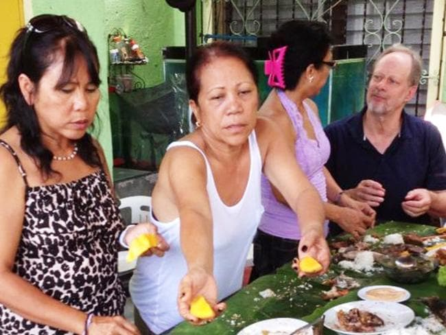 Las Vegas shooter Stephen Paddock (right, black shirt) sharing a meal with Marilou Danley's family in Manilla in 2013. Picture: Supplied