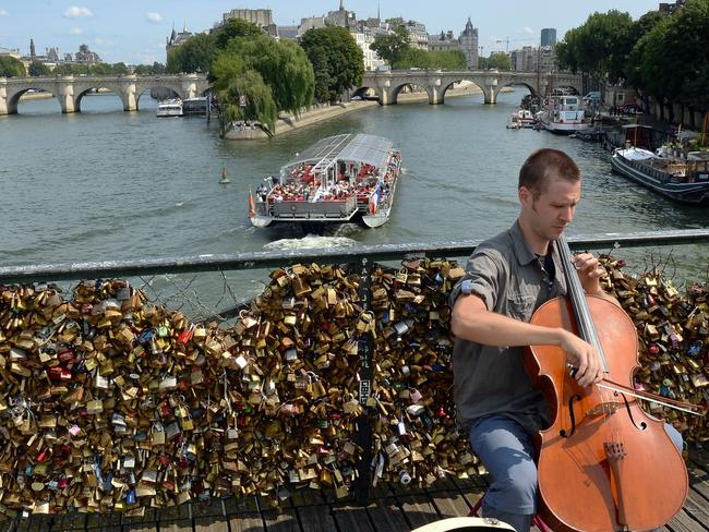 Eyesore? ... A cellist plays on a bridge in front of the love padlocks above the Seine. Picture: AFP