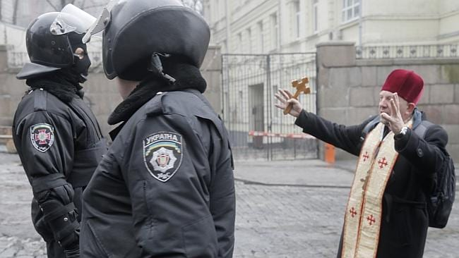 A plea for peace ... A priest addresses police officers to try stop fighting near the Cabinet of Ministers in the centre of Kiev. Picture: AP Photo/Efrem Lukatsky