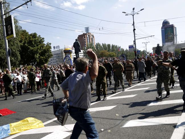 A man throws a projectile and people watch as captured Ukrainian soldiers walk on Lenin square in Donetsk, eastern Ukraine, during a parade in mockery of the country's Independence Day celebrations. Picture: Max Vetrov