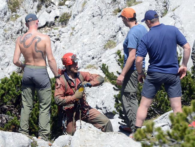 Difficult operation ... a cave and mountain rescue expert from Germany, second left, talks to his colleagues after his descent into the cave.