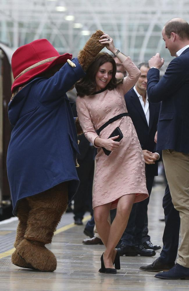 Prince William looks on as wife Kate dances with Paddington Bear at Paddington Station in London. Picture: Jonathan Brady/Pool via AP