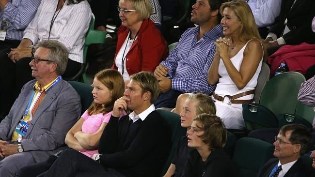 Shane Warne and his family watch the Roger Federer charity match at Rod Laver Arena, with Catriona Rowntree in the background.