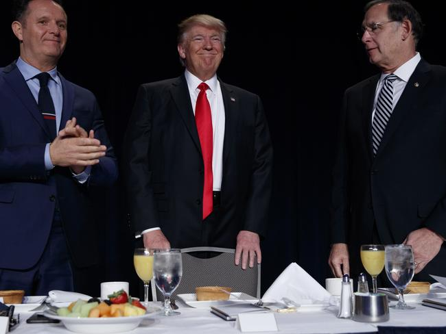 Television producer Mark Burnett, left, and Senator John Boozman watch as President Donald Trump arrives for the National Prayer Breakfast. Picture: AP