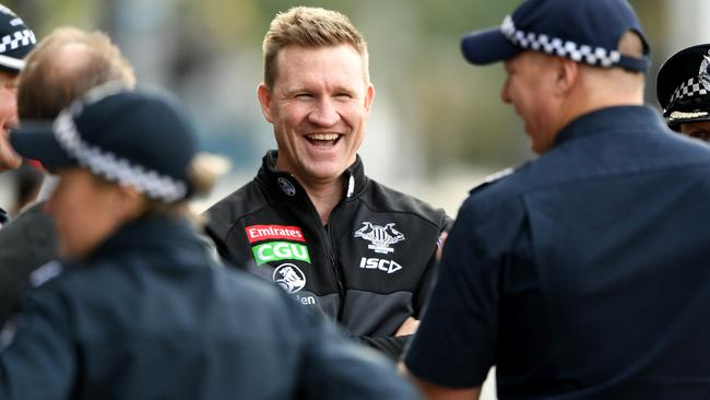 Collingwood AFL coach Nathan Buckley chats with members of Victoria Police, during the Magpies training session in Melbourne, Tuesday, July 25, 2017. In celebration of Multicultural Round, amateur players from the South Sudanese community and Victoria Police will take part in a curtain raiser match at the MCG on Sunday. (AAP Image/Joe Castro) NO ARCHIVING