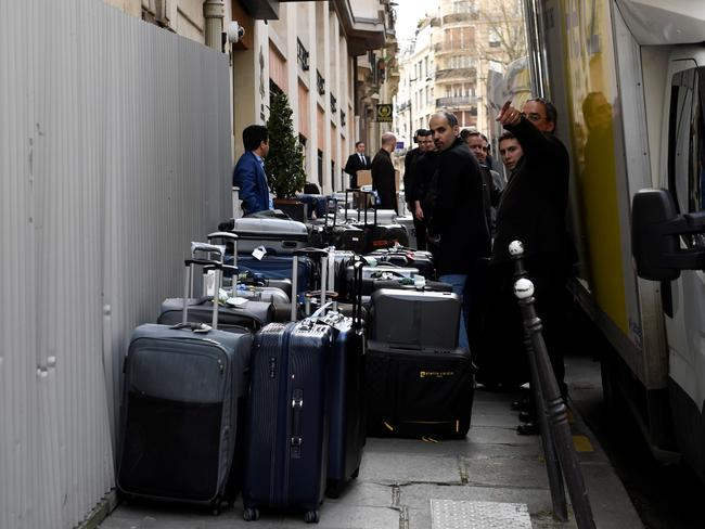People unload luggage for Saudi Arabia's crown prince Prince Mohammed bin Salman's visiting delegation on April 4, 2018, near the Champs Elysee in Paris. Saudi Arabia's crown prince Prince Mohammed bin Salman arrived in France on April 8, for the next leg of a global tour aimed at reshaping his kingdom's austere image as he pursues his drive to reform the conservative petrostate. / AFP PHOTO / Eric FEFERBERG