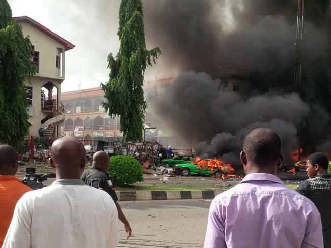 Tragedy ... People watch as smoke fills the sky, after an explosion, at a shopping mall, in Abuja.