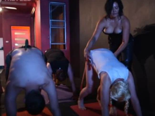 Mistress Anna helping her cross-dressing participant into the Downward Dog pose. Picture: SBS/The Feed.