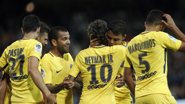 PSG's Neymar, center right back to camera, is congratulated by teammates Dani Alves.