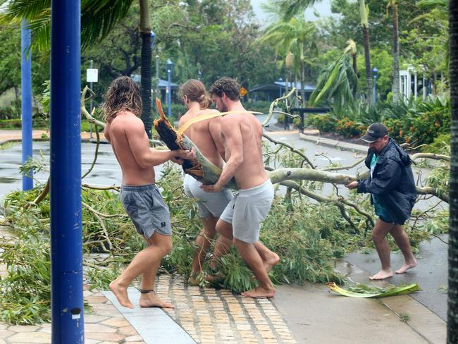 Airlie Beach locals Jayden Thacknay, 20, Raih Woodley, 22, and Rasa Lackey, 20, remove fallen branches from the main street as the eye of cyclone Debbie passes over. Picture: Liam Kidston