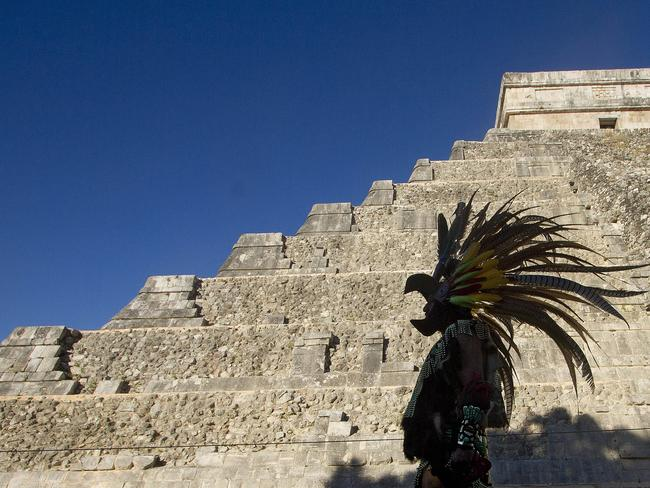 A Mexican man wearing a pre-hispanic costume walk next to the kukulkan pyramid at the Chichen Itza archaeological park, in Yucatan state, Mexico. The pyramid is the subject of a new hi-tech survey. Picture: AFP