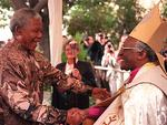 PIRATE: Archbishop Desmond Tutu greets /Pres Nelson Mandela (L) at entrance of St (Saint) George's Cathedral in Cape Town 23/06/96 as he arrives to attend final service to mark Tutu's retirement as Archbishop of Cape Town.