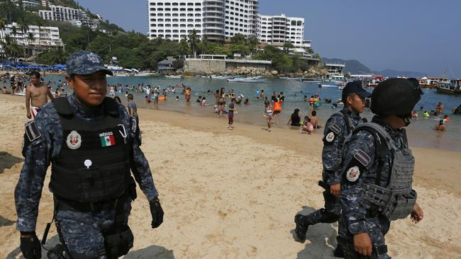 Federal police officer patrol Caleta beach crowded with local residents and tourists in Acapulco. Picture: AP Photo/Enric Marti
