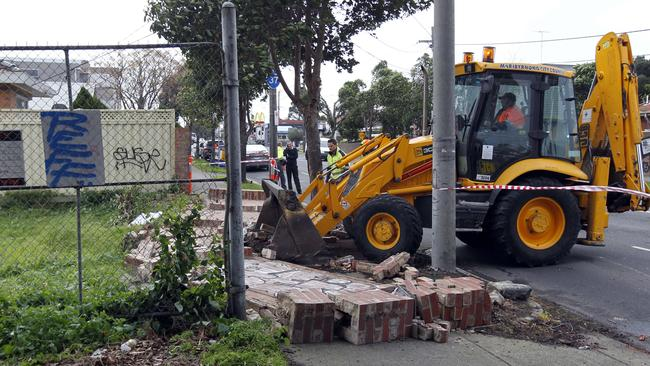 A woman was hurt when high winds caused a wall to collapse in Williamstown Rd, Yarraville. Picture: Richard Serong
