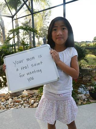 Meika, who was adopted from China in 2008, holds up a sign with one of the damaging comments that have been said about her and her family. Picture: Facebook/Kim Kelley-Wagner Images