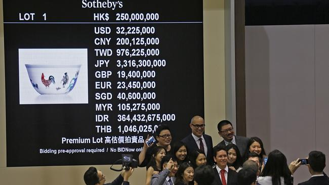 """Payday... Staff members of Sotheby's take a group picture after the auction of Meiyintang """"Chicken Cup"""" from the Chinese Ming Dynasty. Picture: Vincent Yu"""