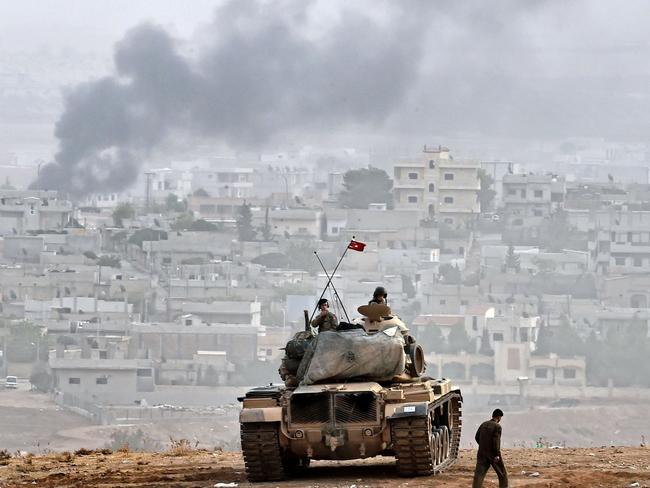 Standing guard ... Turkish soldiers on a tank sit opposite the Syrian town of Ain al-Arab, known as Kobane by the Kurds, at the Turkish-Syrian border. Picture: AFP / ARIS MESSINIS