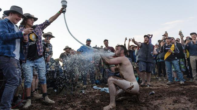A man is seen stripped naked and taking a hit from a gas powered beer pipe
