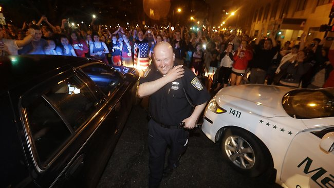 A police officer reacts to news of the arrest of one of the Boston Marathon bombing suspects in Boston. Picture: AP