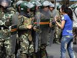 <p>An Uighur woman protests before a group of paramilitary police in Urumqi. Picture: AP</p>
