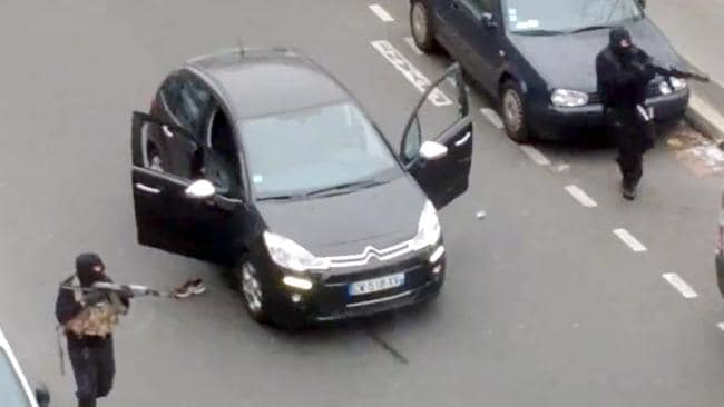 Hooded gunmen aiming Kalashnikov rifles towards a police officer before shooting him dead after leaving the office of the satirical weekly newspaper Charlie Hebdo. Pic: AFP PHOTO/ JORDI MIR