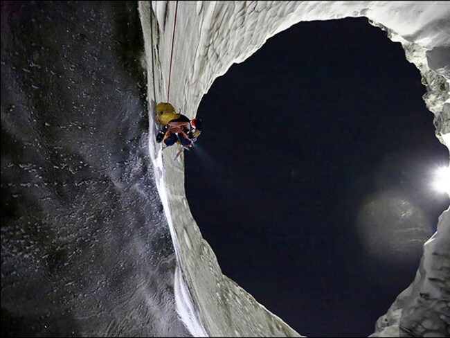 Into the maw ... A researcher scales the side of one of the blow holes to examine the methane lake below. Source: Siberian Times