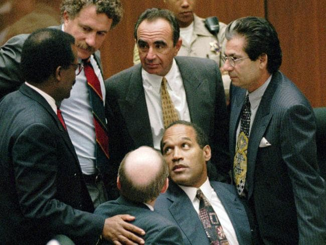 "Acquitted ... OJ Simpson is surrounded by his ""Dream Team"" defence attorneys from left, Johnnie L. Cochran Jr., Peter Neufeld, Robert Shapiro, Robert Kardashian, and Robert Blasier, seated at left."
