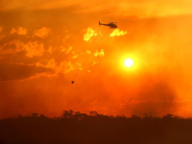 Helicopters water bomb the bush fire at Alfords Point and Menai on Sunday. Picture: Damian Shaw