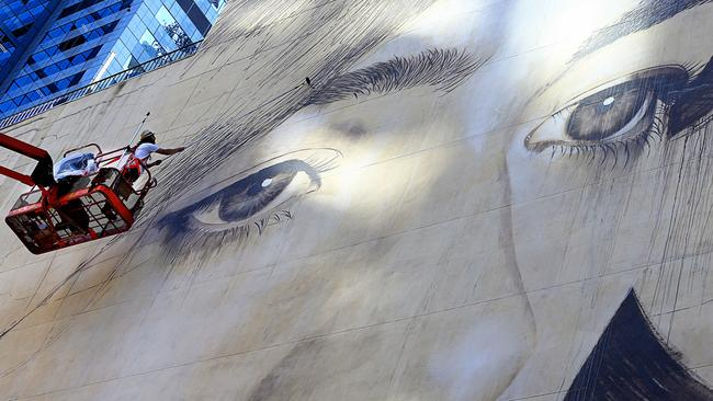Final touches are added to a huge mural of a face on Collins Street, Melbourne e. Picture: Tim Carrafa