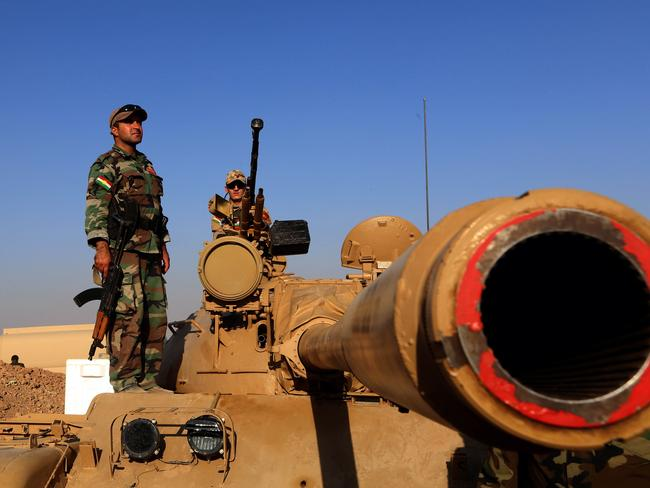 Waiting ... Iraqi Kurdish Peshmerga fighters take position on a tank on the front line in Khazer, near the Kurdish checkpoint of Aski kalak, 40km West of Arbil, the capital of the autonomous Kurdish region of northern Iraq. Picture: AFP