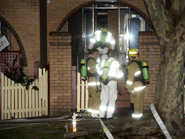 Police and fire crews don breathing apparatus before entering the premises. Picture: John Appleyard