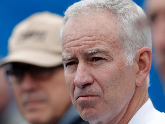Former US tennis player John McEnroe watches as Australia's Bernard Tomic returns to Canada's Milos Raonic during their men's singles semi-final match in the ATP Aegon Championships tennis tournament at the Queen's Club in west London on June 18, 2016.  Raonic won the match 6-4, 6-4. / AFP PHOTO / ADRIAN DENNIS