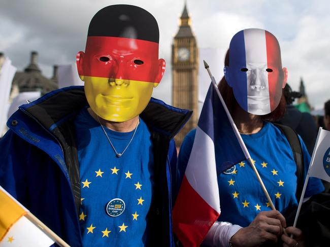 "(FILES) This file photo taken on February 20, 2017 shows protesters wearing German and French flag face masks pose for a photograph during a ""Flag Mob"" demonstration in Parliament Square in central London on February 20, 2017, part of a national day of action in support of migrants in the UK.  EU migrants said on June 23 that far from being ""generous"", Prime Minister Theresa May's offer for their post-Brexit residency was niggardly and left them prey to the whims of British lawmakers. One year ago today on June 23, 2016 Britain voted to leave the European Union. / AFP PHOTO / Justin TALLIS"