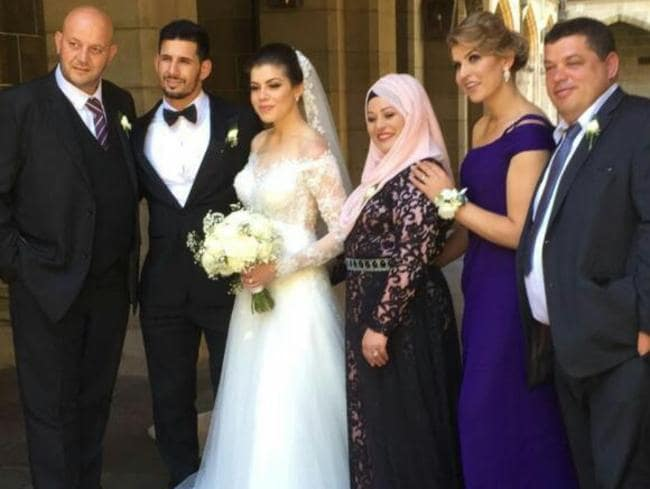 A man strongly resembling Comanchero national president Mick Murray (far left) stands next to Hasan Topal and his bride Samantha Rabah. Picture: Facebook