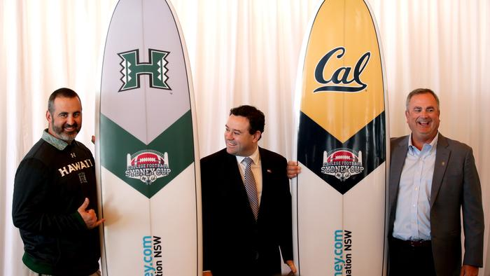 Rainbow Warriors coach Nick Rolovich and Golden Bears coach Sonny Dykes with gifts they recieved from Sports Minister Stuart Ayres. Picture: Gregg Porteous.