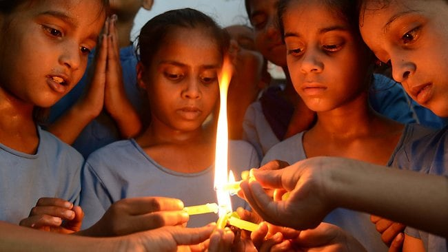 Indian school children light candles as they pay tribute to school children that died from food poisoning in Saran district of Bihar state, at a government school in Amritsar.