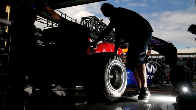 Red Bull roll Ricciardo's car into the garage during testing.