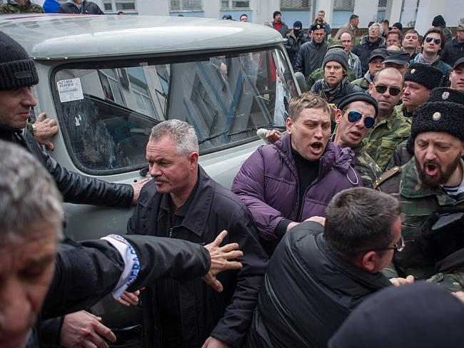 "Crimean Pro-Russian ""self-defence"" forces brawl with Ukrainian servicemen outside the Ukrainian navy headquarters in Sevastopol, Crimea. The pro-Russian forces have taken possession of the base without resistance a day after Russia signed a treaty to annex the region. Picture: AP"