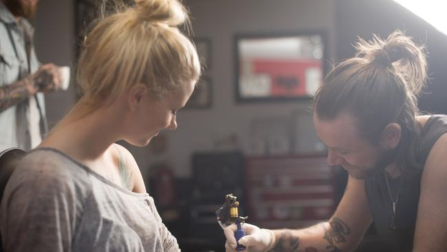 A photo of artist making tattoo on female customer's hand. Tattoo expert is working in studio. Woman looking at man tattooing her hand.