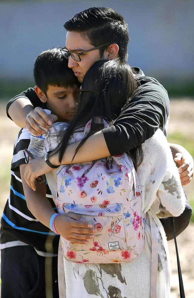 Three siblings embrace after the shooting.
