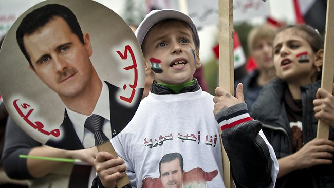 Children of the Syrian community in Romania shout pro-regime slogans while holding pictures of Syrian President Bashar Assad.