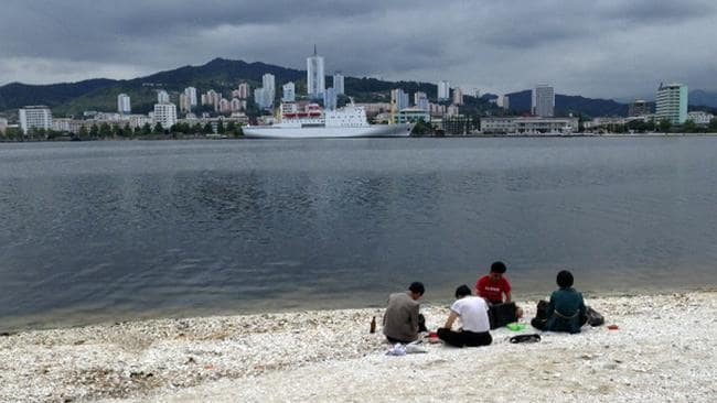 North Koreans picnic in a beach looking across to the city of Wonsan, North Korea. There are plans to develop a world-class beach resort, including an underwater hotel, in the region. Picture: AP