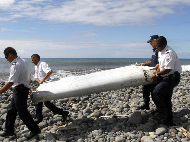 Officers carrying a flaperon washed ashore in eastern La Reunion island. Picture: EPA